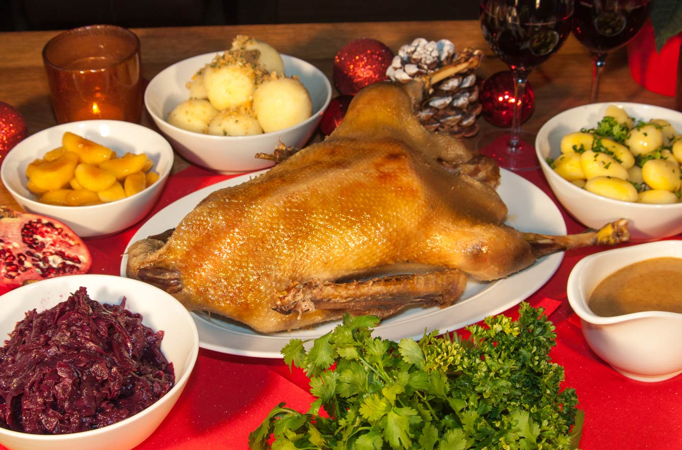 Festlich gedeckter Tisch mit Weihnachtsgans und Beilagen