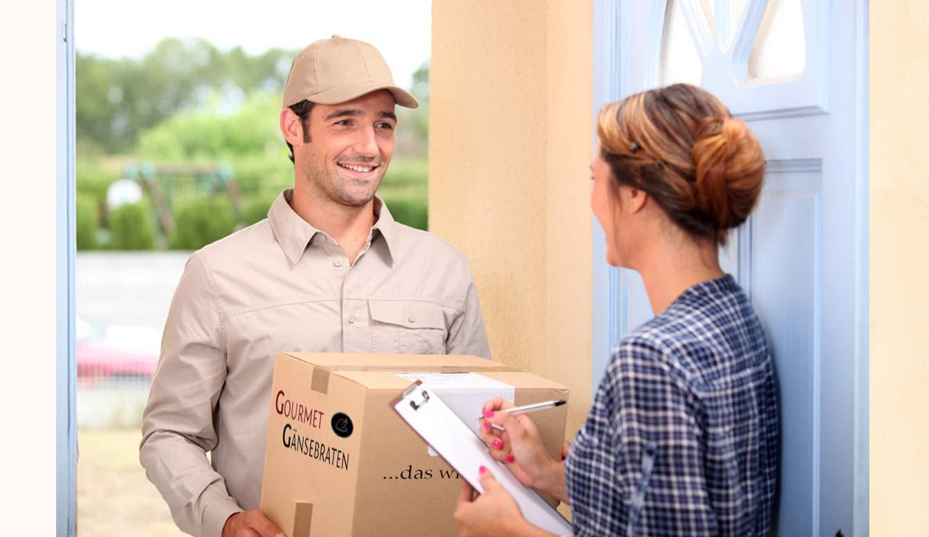 Paketbote, der einer Kundin ein Gourmetgänsebraten-Paket überreicht